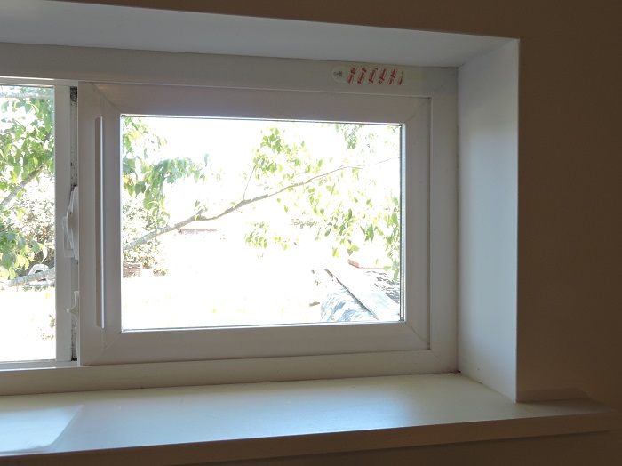 window with command strip attached to the top of frame