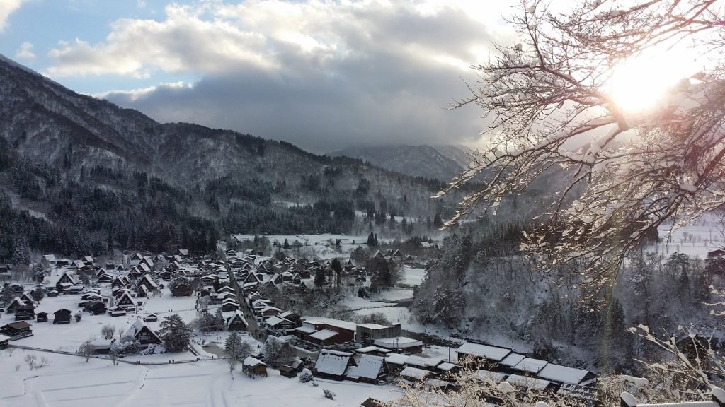 sunlight over the snow covered village of shirakawago