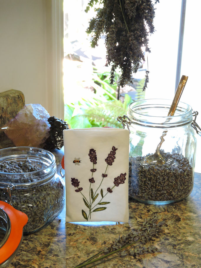 filling the embroidered sachet with dried lavender