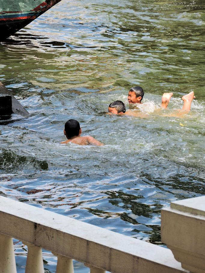 three kids swiming in Bangkok canal