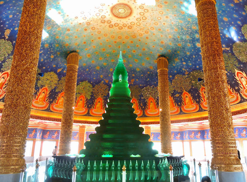 interior of ornate stupa with green crystal and gold pillars