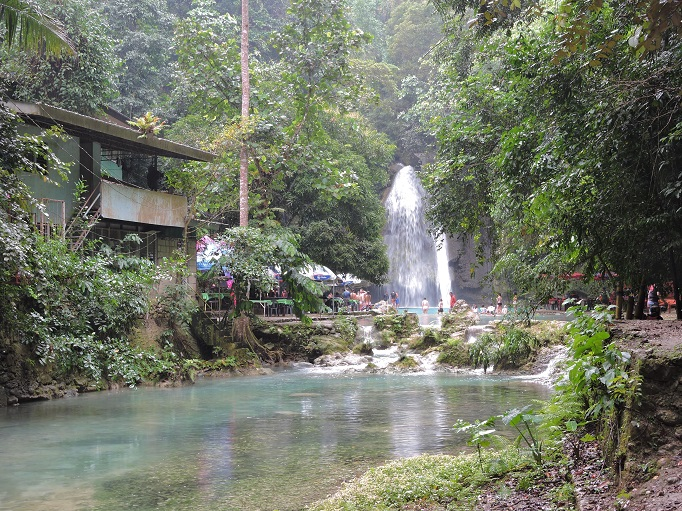 view approaching Kawasan falls with people and buildings