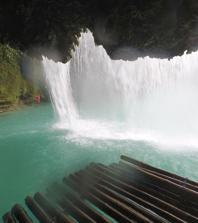 looking out from cave of falls on a bamboo raft