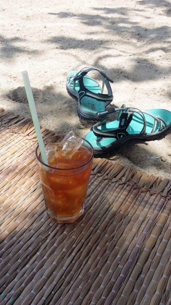 sandals and icetea on beach sand