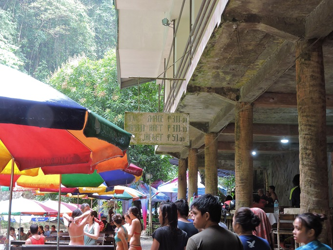 lots of people and table umbrellas at Kawasan with sign for renting