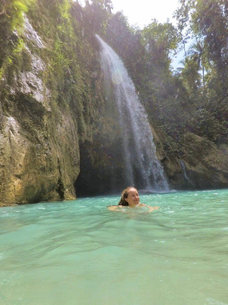 swiming in turquoise blue water jungle behind Inambakan waterfall