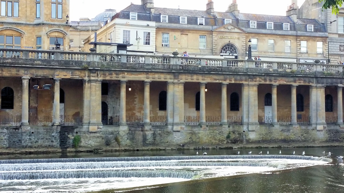 golden limestone buildings along river