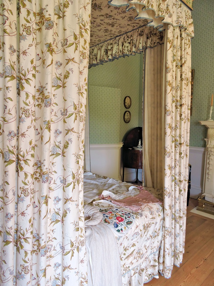 room with canopy bed and wall panel door