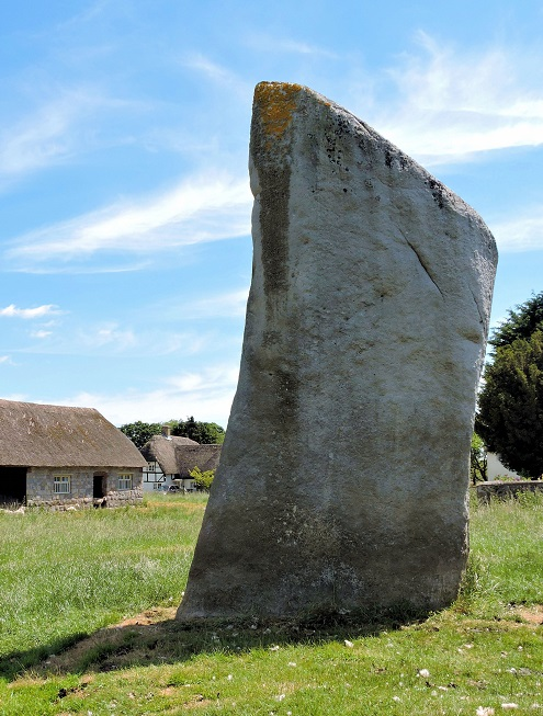 one large stone in front of thatched barn