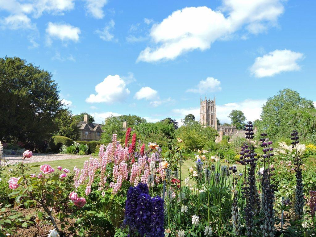lush flower garden stone abbey in background