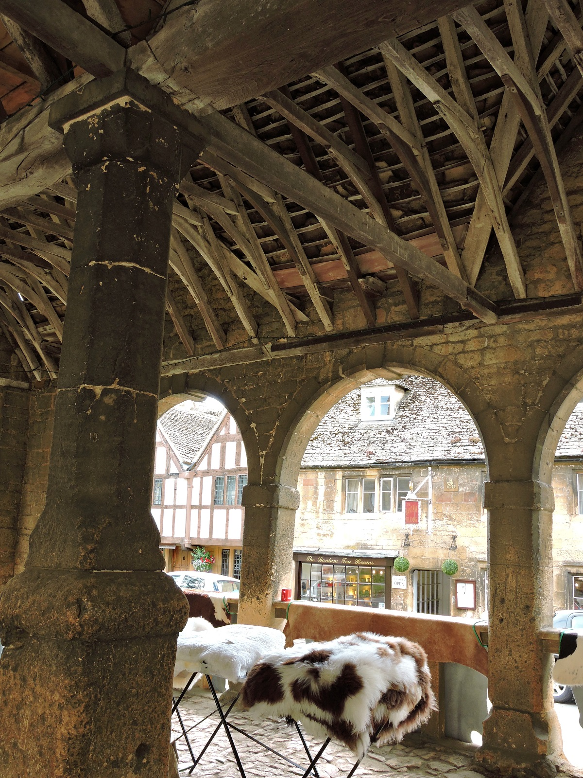 old stone and timber market hall with sheep skins for sale