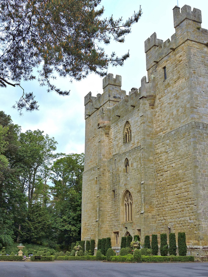 side angle view of Langley castle with trees and hedges
